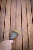 Malerpinsel in der Hand und Malerei auf Holztisch lizenzfreies stockfoto