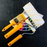 Malerpinsel, Farbenrollen und bunte Farbenproben auf dunklem BAC Stockbilder