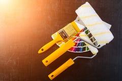 Malerpinsel, Farbenrollen und bunte Farbenproben auf dunklem BAC Lizenzfreie Stockfotos