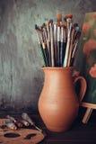 Malerpinsel im Krug, in der Palette, in den Farbenrohren und in der Malerei Lizenzfreies Stockfoto