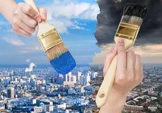 Malerpinsel malt blaue saubere und dunkle schmutzige Stadt Stockfotos
