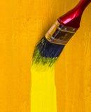 Malerpinsel mit hölzerner Wand der gelben Farbenfärbung Lizenzfreie Stockfotos