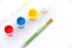 Malerpinsel mit vibrierender roter, gelber, blauer und weißer Farbe Stockfotografie