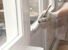 Malerpinsel mit weißem Lack in der Hand Stockfoto