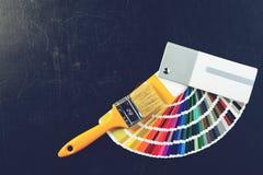 Malerpinsel und bunte Farbenproben auf dem dunklen Hintergrund, getont Stockfotos
