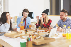 Males and females eating at workplace. Attractive young males and females eating pizza and drinking juice in office. They are having lunch or celebrating Royalty Free Stock Images