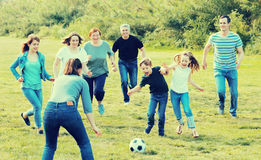 Males and females kicking the ball. Cheerful males and females kicking the ball on green lawn Royalty Free Stock Images