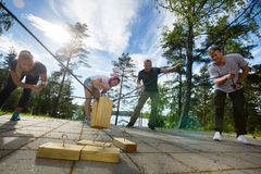 Males And Females Picking Up Wooden Blocks With Ropes. On patio in forest Royalty Free Stock Photo