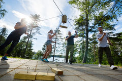 Males And Females Picking Wooden Blocks With Ropes. Low angle view of males and females picking wooden blocks with ropes on patio in forest Royalty Free Stock Photography