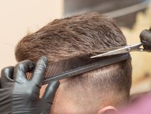 Free Males Hair Cutting With Comb And Scissors, Close Up View. Hairstylists Hands In Black Rubber Gloves Cutting Hair With Royalty Free Stock Image - 156753036