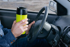 Males hand holding thermo mug. Close up of male`s hand holding thermo mug with hot coffee driving in a car Stock Images