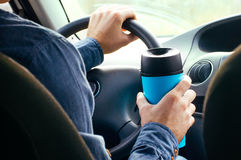 Males hand holding thermo mug. Close up of male`s hand holding thermo mug with hot coffee driving in a car Royalty Free Stock Image