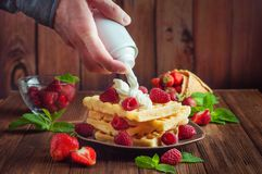 Males hand putting whipped cream on belgian waffle stock photography
