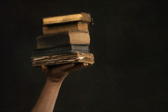 Males Hand with Stack of old Books Stock Images