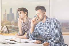 Males talking on phone at workplace. Two handsome caucasian males working on project and talking on phone at workplace Stock Image