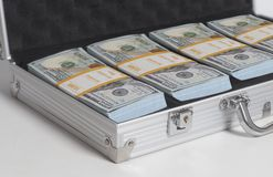 Maleta abierta con cientos pilas de los billetes de dólar imagen de archivo