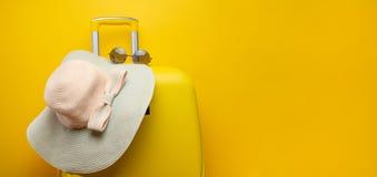 Maleta amarilla de la bandera, con un sombrero para la reconstrucción, la playa y las gafas de sol Viaje festivo de la aventura d imágenes de archivo libres de regalías