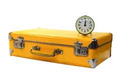 Maleta amarilla vieja con el reloj de alarma verde Fotografía de archivo