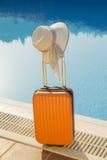 Maleta anaranjada y un sombrero en el poolside Imagen de archivo