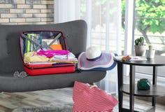 Maleta con diversos ropa y accesorios en el sofá dentro El embalar para las vacaciones Fotografía de archivo libre de regalías
