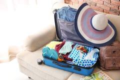 Maleta con diversos ropa y accesorios en el sofá dentro El embalar para las vacaciones Imagen de archivo