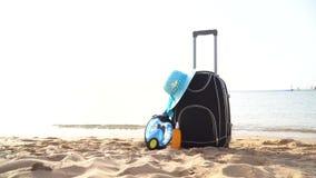 Maleta de las vacaciones del día de fiesta del viaje con crema, el sombrero de paja y la máscara del salto en la playa hermosa An almacen de video