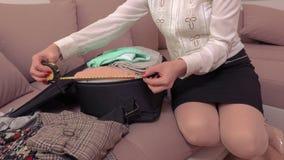 Maleta de medición de la mujer en casa antes del viaje metrajes