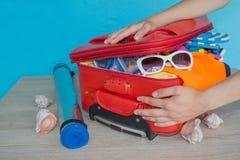 Maleta del embalaje de la chica joven en casa Abra la maleta llena para viajar Foto de archivo