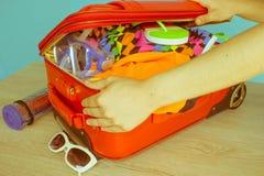 Maleta del embalaje de la chica joven en casa Abra la maleta llena para viajar Fotografía de archivo libre de regalías