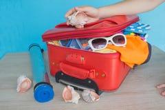 Maleta del embalaje de la muchacha en casa Maleta abierta llena para viajar, ascendente cercano Imágenes de archivo libres de regalías