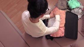 Maleta del embalaje de la mujer en la opinión superior de la cama en casa metrajes
