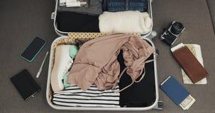 Maleta del embalaje de la visi?n superior Manos femeninas que ponen cosas del verano en una maleta Concepto del viaje por carrete almacen de video