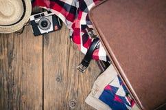 Maleta del viaje con ropa, la cámara vieja y el sombrero de paja en la tabla de madera Fotos de archivo