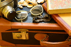 Maleta del vintage, cámara, gafas de sol, conchas marinas, pulsera y una pila de libros El viajar del vintage Fotos de archivo libres de regalías