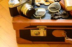 Maleta del vintage, cámara retra, gafas de sol, conchas marinas, pulsera y una pila de libros El viajar del vintage Imágenes de archivo libres de regalías