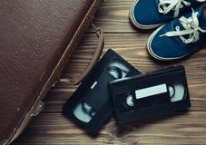 Maleta del vintage, cintas de video y zapatillas de deporte de cuero en un piso de madera Visión superior imagen de archivo libre de regalías