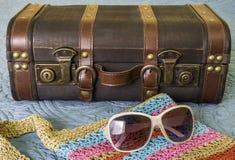 Maleta del vintage, gafas de sol y monedero colorido tejido en la cama, PA fotos de archivo libres de regalías