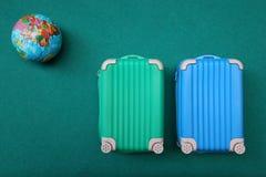 maleta dos con un globo en fondo brillante verde concepto del recorrido foto de archivo