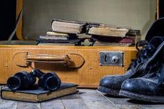 Maleta elegante vieja Zapatos fangosos militares en una maleta Maleta en una tabla de madera Imágenes de archivo libres de regalías