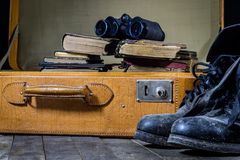 Maleta elegante vieja Zapatos fangosos militares en una maleta Maleta en una tabla de madera Imagenes de archivo