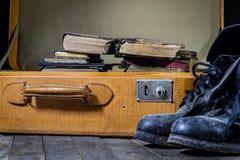 Maleta elegante vieja Zapatos fangosos militares en una maleta Maleta en una tabla de madera Fotos de archivo libres de regalías