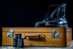 Maleta elegante vieja Zapatos fangosos militares en una maleta Maleta en una tabla de madera Fotografía de archivo libre de regalías