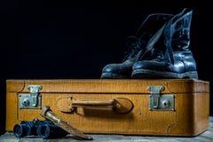 Maleta elegante vieja Zapatos fangosos militares en una maleta Maleta en una tabla de madera Fotografía de archivo