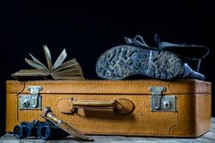 Maleta elegante vieja Zapatos fangosos militares en una maleta Maleta en una tabla de madera Imagen de archivo libre de regalías