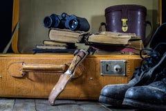 Maleta elegante vieja Zapatos fangosos militares en una maleta Maleta en una tabla de madera Foto de archivo libre de regalías