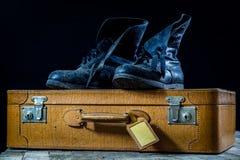 Maleta elegante vieja Zapatos fangosos militares en una maleta Maleta en una tabla de madera Imagen de archivo