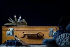 Maleta elegante vieja Zapatos fangosos militares en una maleta Maleta en una tabla de madera Foto de archivo
