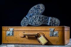 Maleta elegante vieja Zapatos fangosos militares en una maleta Maleta en una tabla de madera Fotos de archivo