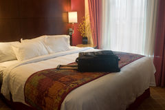 Maleta en cama del hotel Imagen de archivo