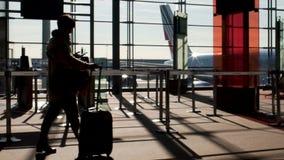 Maleta femenina del balanceo en el terminal de aeropuerto, teléfono móvil de la tenencia, viajando al extranjero almacen de video